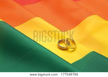 Two wedding rings on rainbow gay flag background