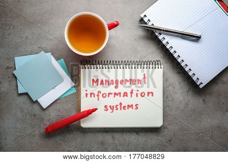 Notebook with written text MANAGEMENT INFORMATION SYSTEMS on texture background