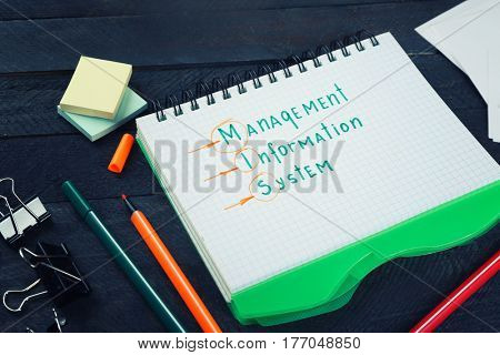 Notebook and stationery on dark wooden table. Management concept