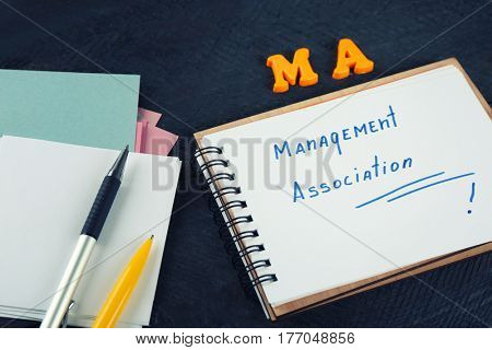 Notebook and stationery on black wooden table. Management concept