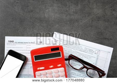 Calculator with documents and cellphone on table. Tax concept