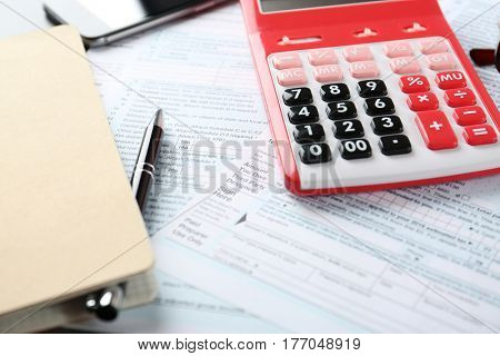 Calculator with documents and stationery on table. Tax concept