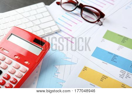 Calculator with documents and keyboard on table. Tax concept