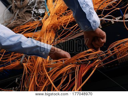 Hands of young engineer connecting cables in server room