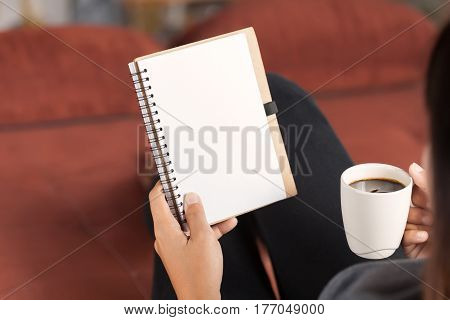 selective focus on woman reading notebook and holding coffee cup in morning