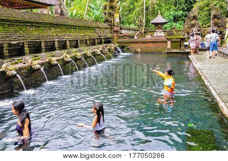 Bali,Indonesia-May 29,2010:Balinese worshippers pray in the water at the Tirta Empul Temple Bali,Indonesia on 29th May 2010.They believe that water from the spring is holy & has the healing power.