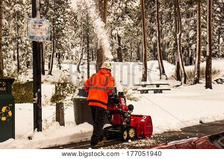 Highway Worker Blowing Snow At Roadside Rest Stop