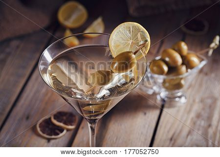 Glass of martini with green olives on a rustic wooden table. Vermouth cocktail.
