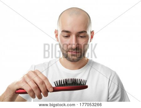 Hair loss concept. Young man with hair comb on white background