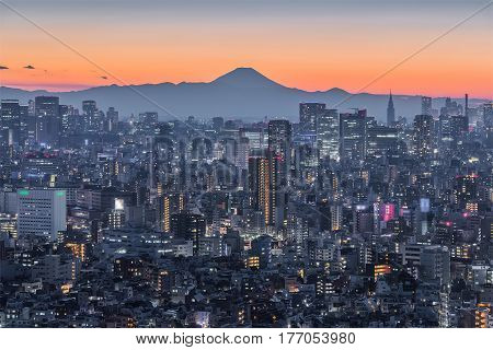 Tokyo night city view with Mountain Fuji. Mount Fuji lies about 100 kilometres south-west of Tokyo and can be seen from there on a clear day.