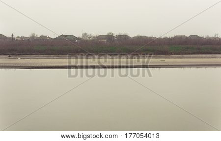 Riverbed on a foggy day. Calm river