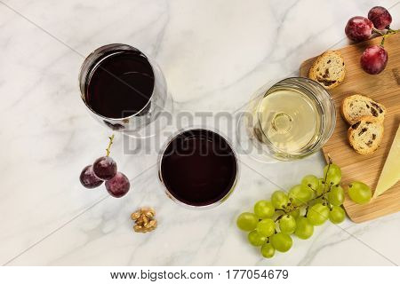An overhead photo of glasses of red and white wine at a tasting, with grapes and a place for text