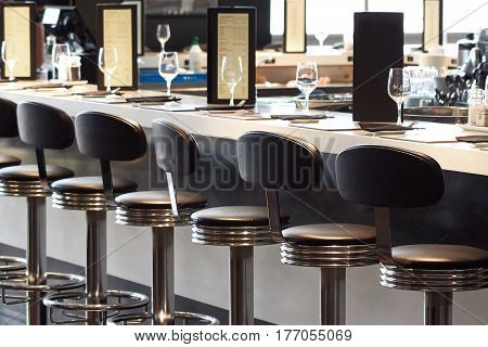 Bar stools and bar desk with glasses and menu cards