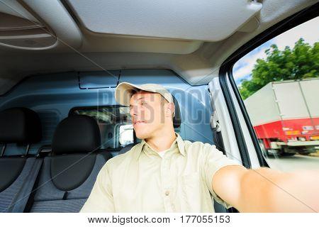 A uniformed messenger in his van, doing his job.