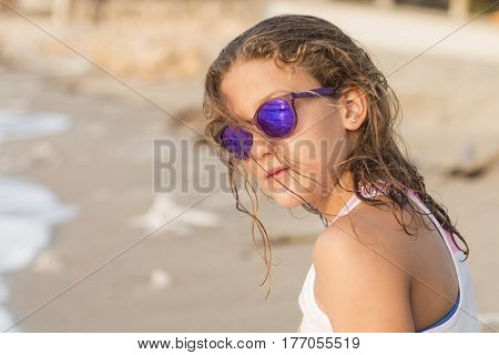 Little girl sunbathing on the beach after bathing.