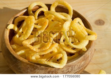 Onion rings chips in a wooden bowl on a Board.