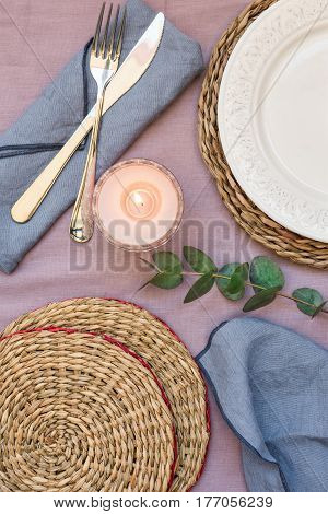 Empty table setting elegant white plate rattan coasters lit candle cutlery blue napkins branch of silver dollar eucalyptus decoration flat lay top view