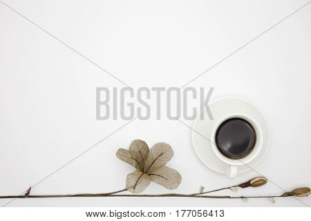 coffee cup with paper flower on white paper background