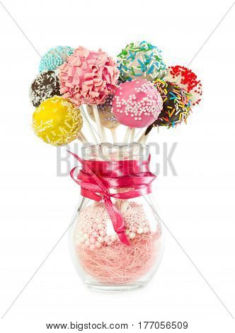 Colorfull cake pops with decorative sprinkles in glass vase isolated on white background