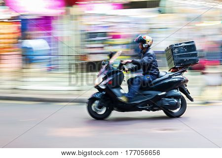 Scooter Messenger On The Road In Motion Blur