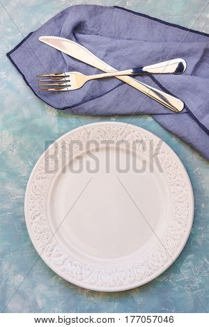 Empty table setting arrangement white plate cutlery blue napkin concrete table surface top view flat lay