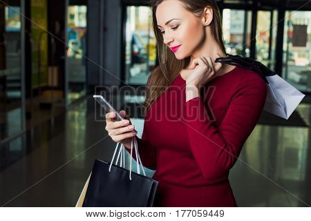 Woman looking in the phone, holding shopping bags while standing in the mall. Shopping lady.