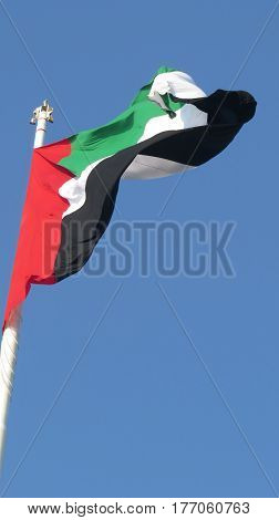 A huge flag of United Arab Emirates - UAE fluttering in the wind against clear blue skies.