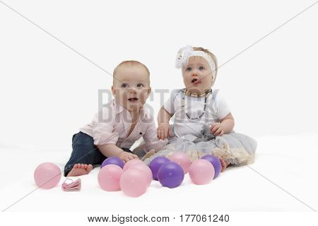 Adorable baby boy and handsome funny girl sitting on the white background. Boy is looking at camera. Girl is looking away