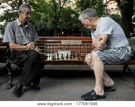 LVIV UKRAINE - AUGUST 19 2015: Old men playing chess on a bench in a park of Lviv