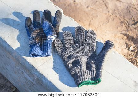he old cloth glove is placed on a concrete pole during the sunny shine to shine.