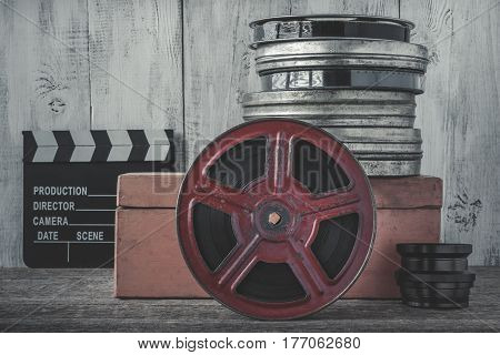 Clapperboard film coils wooden box and lens are on the board