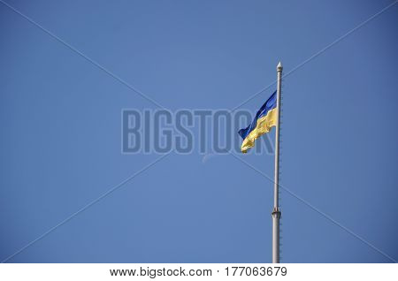 The Ukrainian flag is developing in the wind. Moon in the blue sky