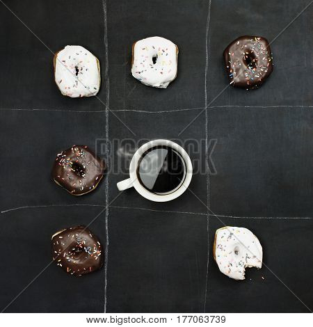 Tic Tac Toe donuts and coffee over black board background. Image shot from overhead.