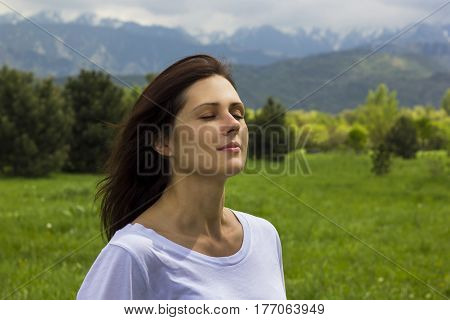 young woman with eyes closed breathing fresh air in the mountains