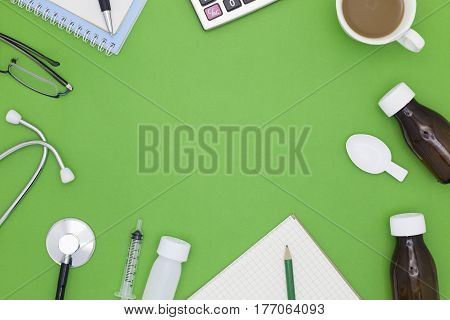 Stethoscope with notebook pen white paper coffee cupglasses bottle of medicinefeeding syringe on green backgroundMedical background concept