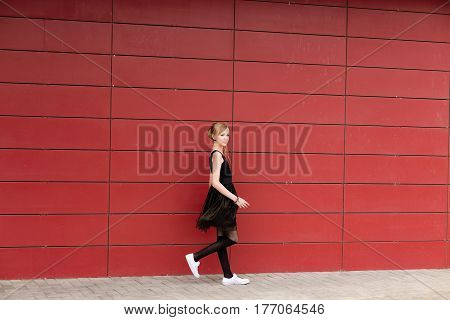 Beautiful Blond Girl In A Black Dress Posing Against A Red Wall