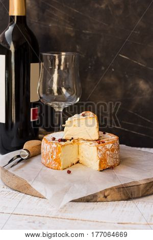 French munster cheese with orange rind red pepper corns cut off slice forkwine bottle and glass rustic style