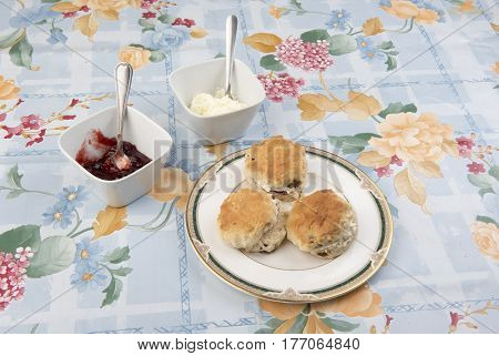 Image of three scones on a plate with pots of cream and jam