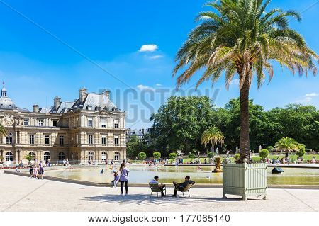 Paris France - Jule 07 2016: People enjoy sunny day in the Luxembourg Gardens in Paris. Traditional small wooden sailing boats in the pond near Luxembourg Palace official residence of the French Senate.
