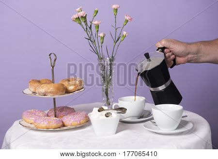 An unrecognisable hand pouring a cup of coffee in a white mug. Taken on a purple background