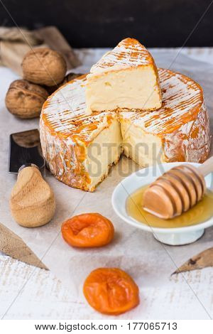 French or German soft cheese of camambert type with orange rind honey dipper dried fruits knife and walnuts on wood table top view