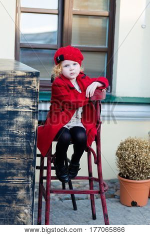 Portrait Of A Beautiful Little Girl With Red Hair In A Red Coat