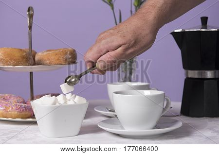 An unrecognisable hand putting a cube of sugar in a coffee cup