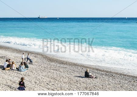 Nice, France - 25 February, A group of people on the beach, 25 February, 2017. People and tourists having a rest on the Cote d'Azur.