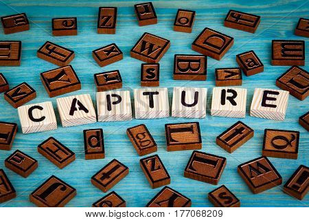 capture word written on wood block. Wooden alphabet on a blue background.
