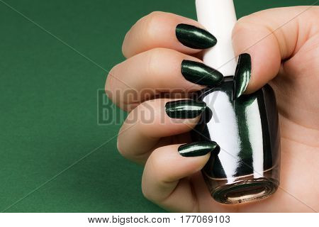 Female hand with dark green nails is holding dark green nail polish on green background.