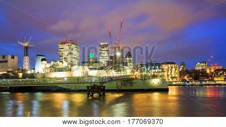 HMS Belfast on the River Thames at dusk in London is a popular tourist location London England 2016