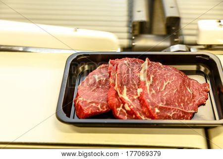 The Meat Processing Plant. The Beef Is Cut Into Steaks Lies In A Plastic Container.