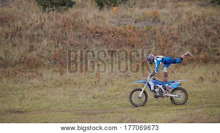 Girl Bike shows acrobatic at MX moto cross racing - rider on a dirt motorcycle, telephoto