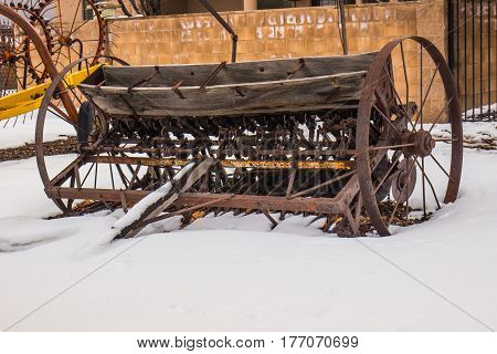 Vintage Farming Equipment With Large Metal Wheels In Wintertime